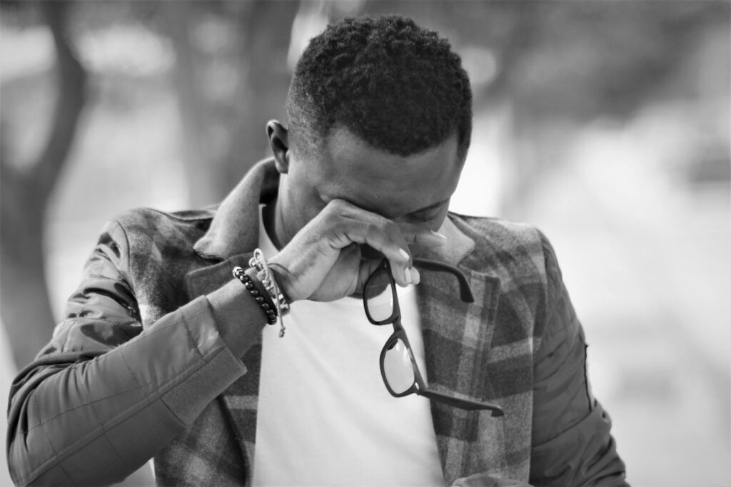 En la imagen se ve un hombre llorando. Se quito sus gafas y se tapa la cara con una mano. Relaciones toxicas pueden causar un momento triste como tal.