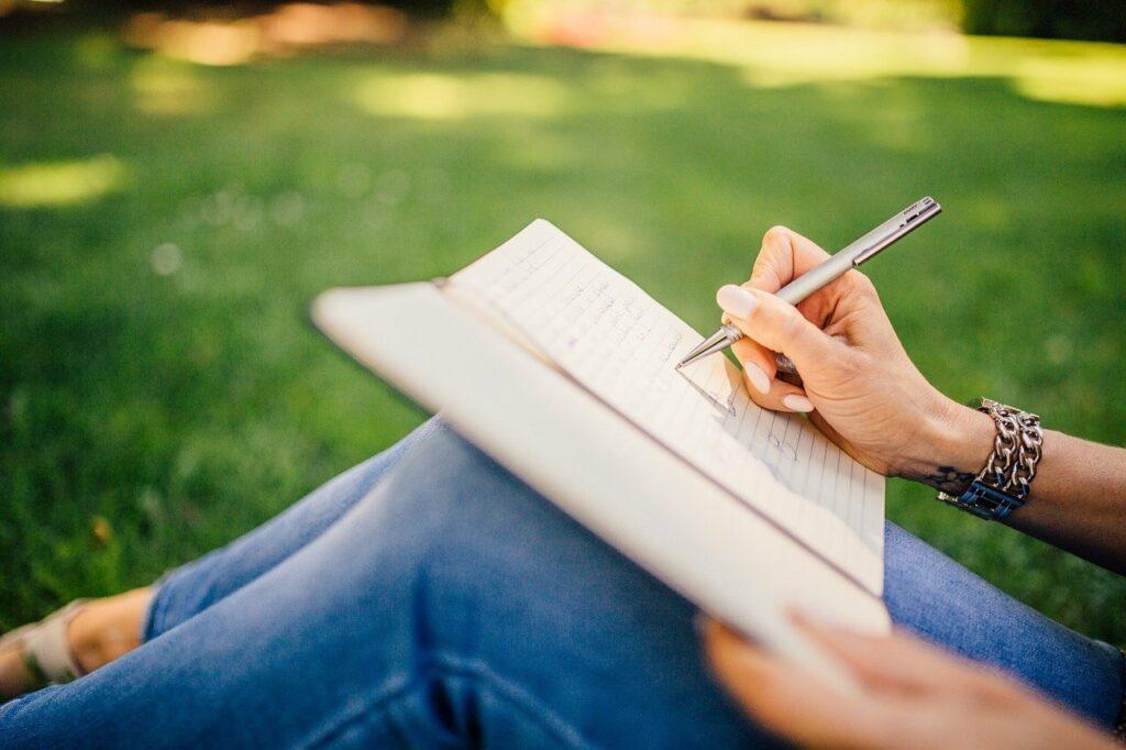 El foco de la imagen esta sobre una mano y un lapiz. Esta escribiendo algo en un cuaderno. La persona esta sentada afuera y se toma su tiempo.