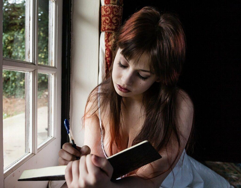 En la imagen se ve una chica joven que esta escribiendo en su diario personal. Sentada al lado de la ventana, con una cara triste, rellena las hojas con pensamientos usando un lapiz.