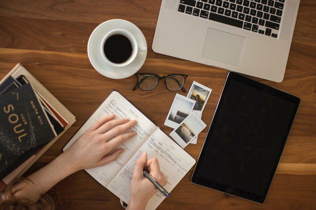En la imagen se ve un persona que esta escribiendo cosas en un cuaderno. Tienes libros a su lado, imagenes personales y otro cuaderno cerrado. Parece que se esta tomando el tiempo para poder escribir sus pensamientos en un diario personal.