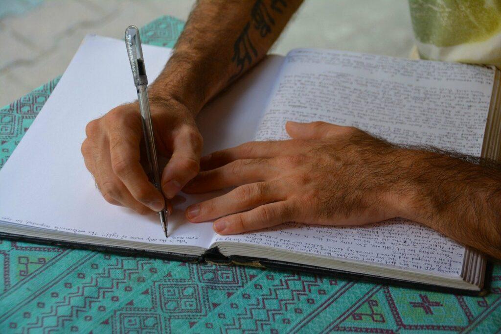 En la imagen se ve alguien que esta escribiendo detalladamente en su diario personal. Con letra muy chica escribe sus pensamientos sobre hojas grandes blancas.
