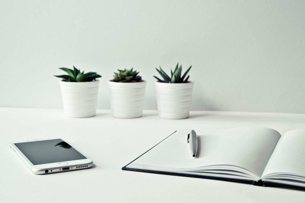 En la imagen se ve un cuaderno abierto sobre una mesa. Un lapiz esta sobre las hojas blancas y un celular a su lado. Todo esta listo para escribir un diario personal.