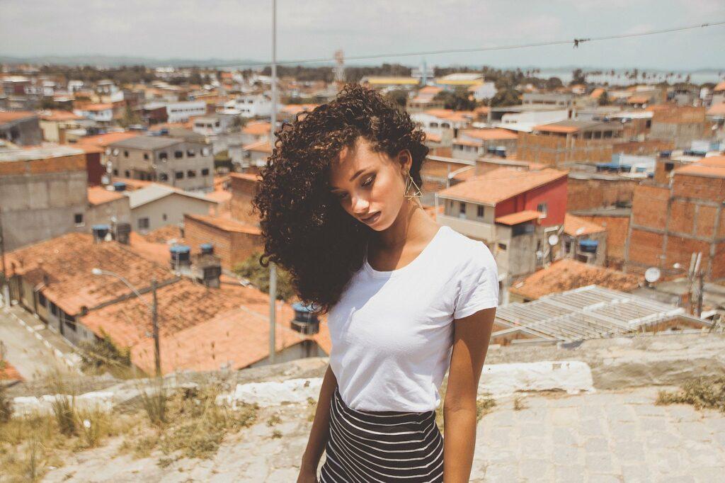 En la imagen se ve una mujer joven, sumamente bella y delicada. Con el pelo ondulado. En el fondo una ciudad que parece ser de sudamerica. Así es la belleza latina. Los contraste la destacan.