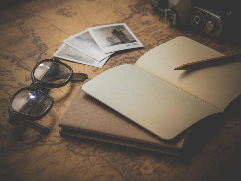 En la imagen se ve un cuaderno abierto con un lapiz, una gafas, polaroids y un mapa como fondo. Parece que estan planeando las proximas vacaciones.