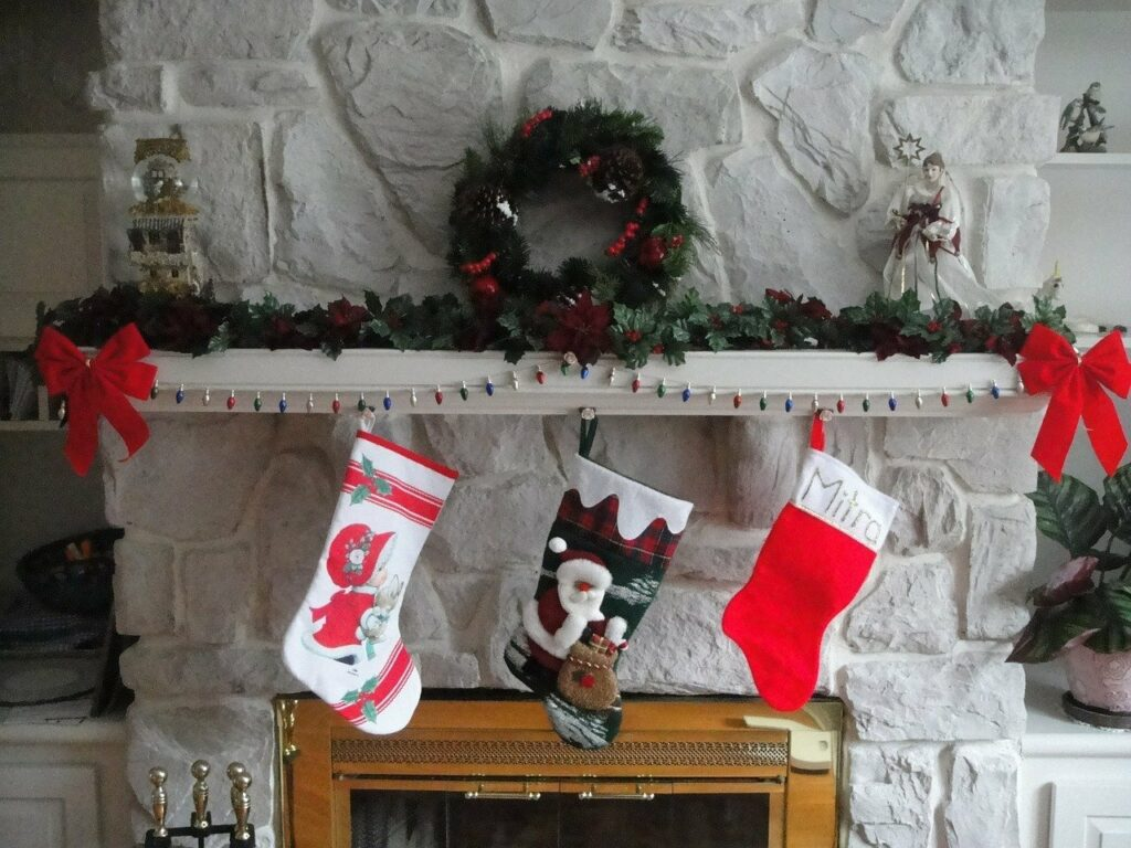 En la imagen se ve una chimenea decorada. Los calcetines de navidad colgados, las guirnaldas en posición y una cadena de luces son decoraciones navideñas que no pueden faltar.