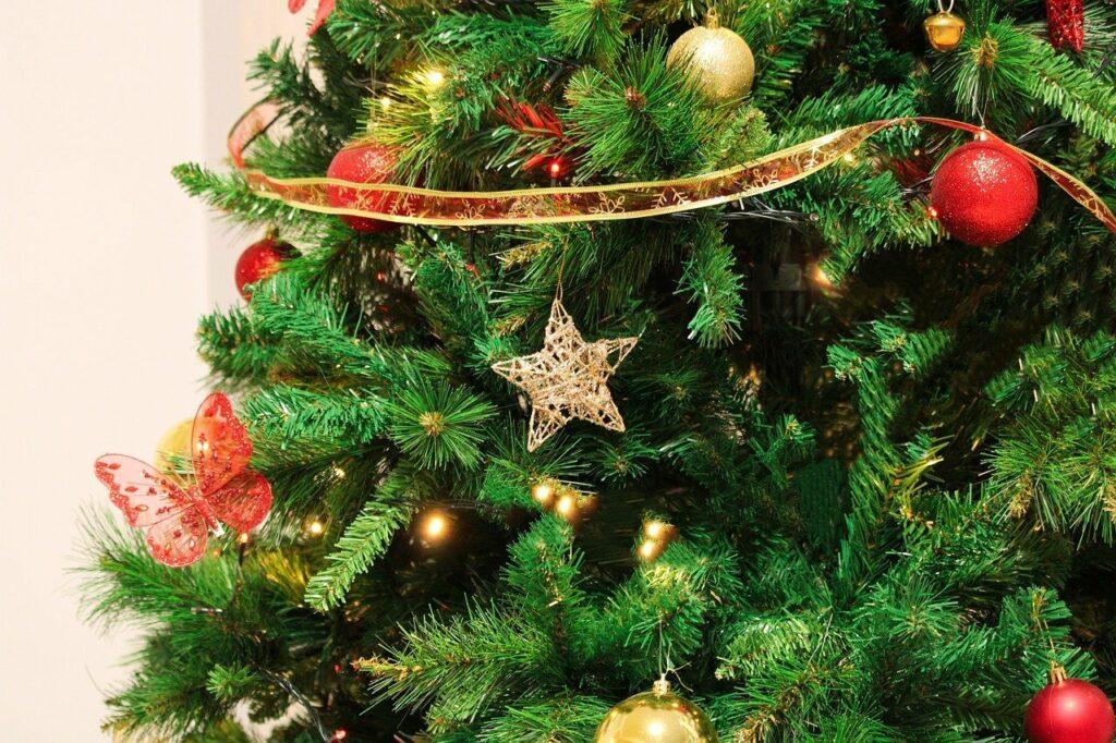 En la imagen se ve parte de un arbol de navidad, decorado y listo para cuidar los regalos.