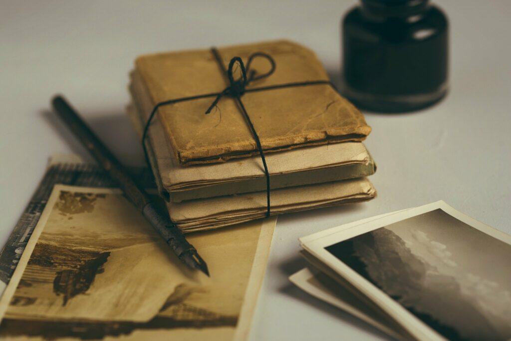 En la imagen se ve un paquete de cartas, viejas y amarillas. Unas fotos alrededor y una pluma vieja y antigua. Pueden ser cartas de amor del abuelo a la abuela.