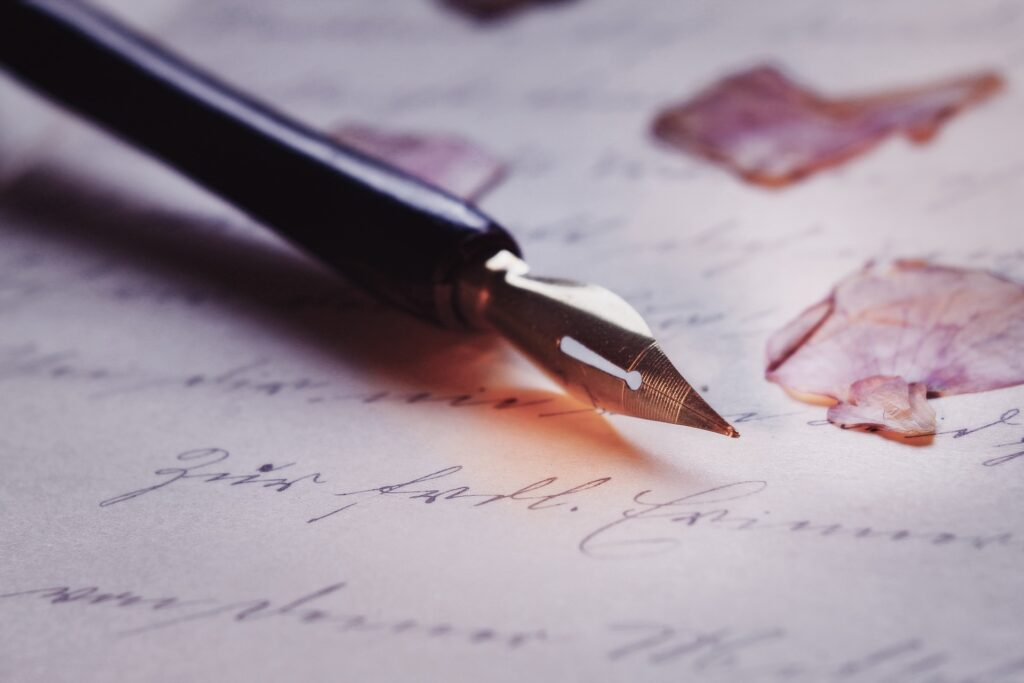 La imagen muestra una pluma sobre un papel de hoja. Palabras fueron escritas y petalos las adornan. Que romantico para la persona que las vaya a leer.