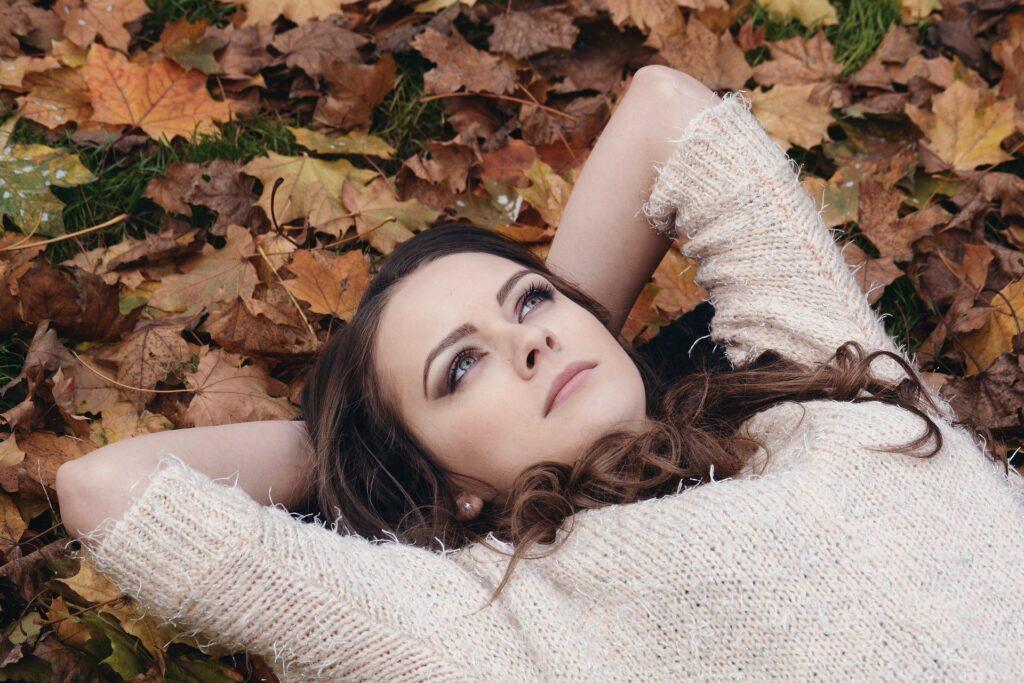 Vemos una mujer joven acostada sobre hojas y pasto. Mira hacia el cielo, una mirada profunda y pensativa.