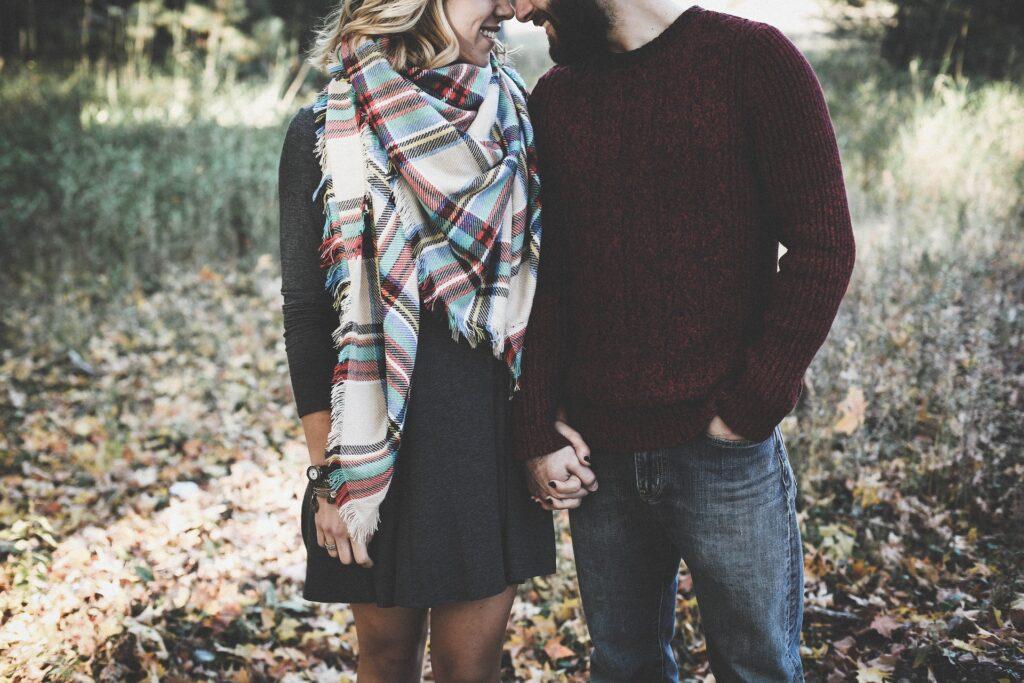 Vemos a un hombre y una mujer, cercanos y tomados de la mano. Estan felices, se nota en sus sonrisas. El sabe cómo seducir a una mujer.
