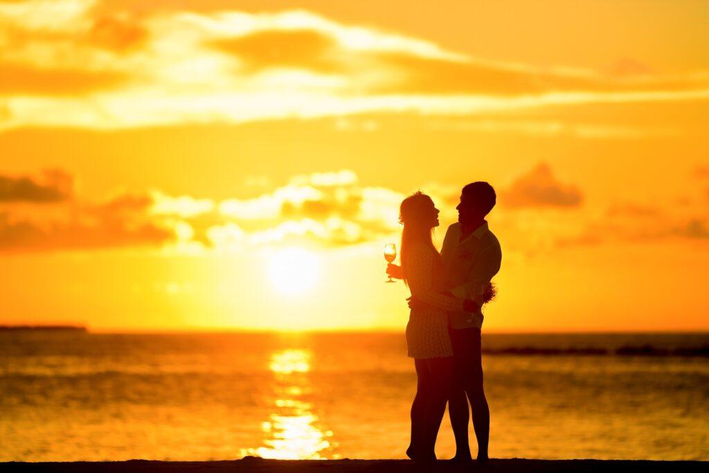 En la imagen vemos un atardecer precioso. Una pareja esta disfrutando del momento y mirandose a los ojos.  Un momento que lleva a más intimidad.