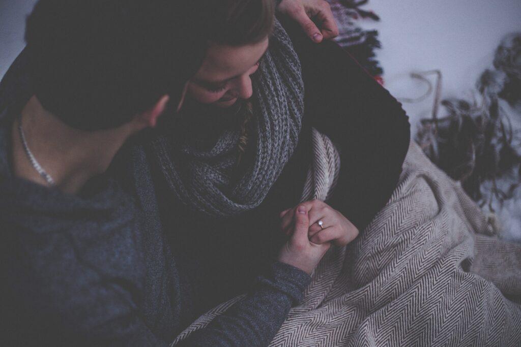 La imagen muestra una pareja sentada y abrazada. Una cobija sobre las piernas. Sostenidos de la mano. La intimidad se puede manifestar de esta manera.