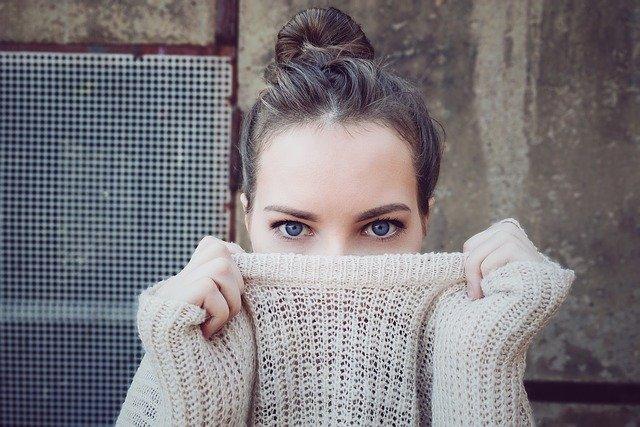 Encontrar a una Sugar Baby - La imagen muestra una mujer joven y atractiva ocultando parte de su rostro con su suéter. Una Sugar Baby ocultándose y esperando a ser encontrada. Tiene ojos azules y el pelo atado.