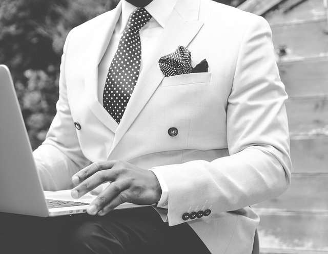 Millonarios solteros también utilizan medios sociales. En la imagen lo podemos ver. Se trata de un hombre vestido de forma elegante. Un traje blanco y espectacular. Utiliza una computadora.