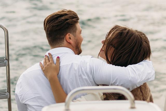 ¿Cómo cautivar a un millonario?: En la imagen vemos a dos personas sentadas juntas y abrazadas. Están sobre un yate disfrutando de la compañía. Así es la vida de un millonario y ella esta más que feliz.