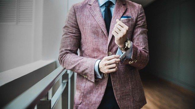 ¿Cómo cautivar a un millonario?: En la imagen vemos el torso de un hombre que esta bien vestido. Lleva puesto un traje de colores llamativos. Es muy elegante.