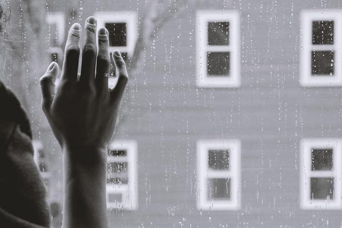 Complejo Paterno: La foto esta en blanco y negro. Una mano contra una ventana de vidrio. Esta lloviendo y la ventana está un poco húmeda. La imagen expresa un momento triste de dolor.