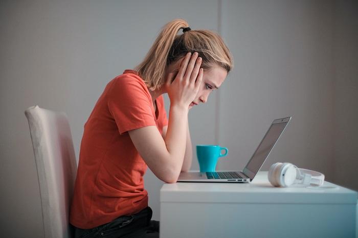 Complejo Paterno: Una mujer joven frente a su computadora. Tiene una mirada triste y melancólica. Parece tener un mal momento. Esta fijada en la pantalla y se tapa los oídos.
