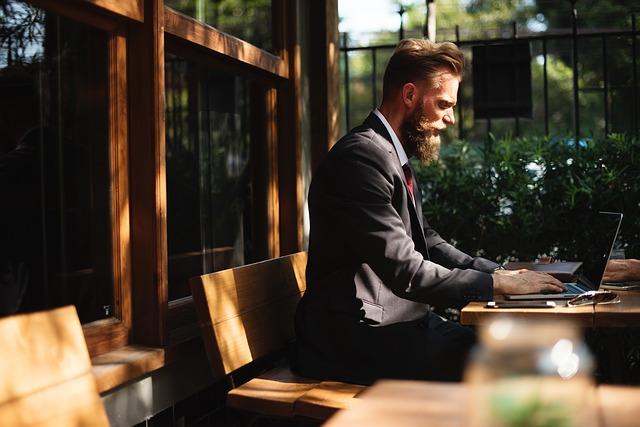 Relaciones virtuales: En la foto vemos a un hombre elegante utilizando su computador. Tiene estilo y lo hace notar en su barba y su corte de pelo. Escribe de forma concentrado en su computadora. Quizás esta conversando con su Sugar Baby.