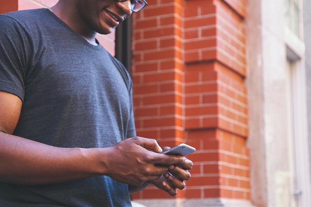 Relaciones virtuales: En la foto vemos a un hombre feliz de haber recibido un mensaje texto a su celular. Tiene una sonrisa en su rostro y esta a punto de responder.