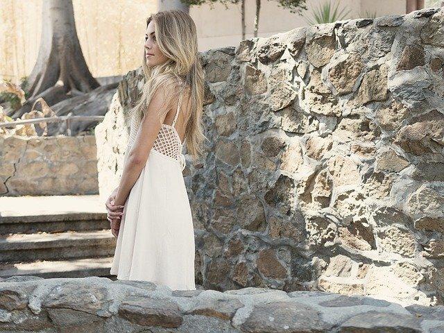Chicas jóvenes: En la imagen vemos a una mujer joven. Lleva puesto un vestido blanco de verano. Es muy bella y tiene un cabello hermoso. Se ve de lado, ya que está observando algo en el horizonte. Parece estar distraída, pero se nota que esta feliz. Puede que su Sugar Daddy este por llegar.