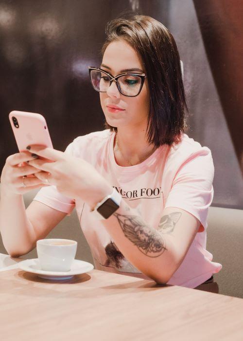 Etiqueta: Vemos a una mujer joven utilizando su teléfono celular. Esta mandando mensajes, seguramente esta respondiendo mensajes a su Sugar Daddy. Con una sonrisa en el rostro es, por seguro, un mensaje lindo.