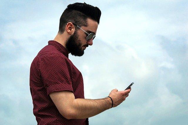 En la imagen vemos a un hombre con un estilo casual, pero elegante. Tiene unos lentes sol y esta mirando sobre su celular. El estilo implica que tiene dinero, es decir, tiene privilegios y vive una vida sin preocupaciones.