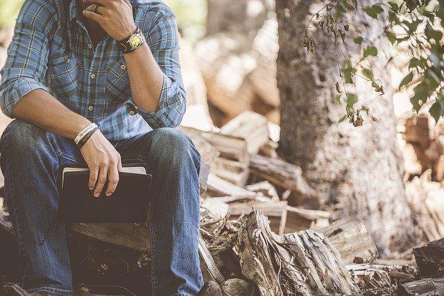 Manual para Sugar Daddies: En la imagen vemos a un hombre sentado. Sostiene un libro en su mano derecha y parece estar pensando. Quizás es un libro sobre relaciones y esta reflexionando sobre las cosas que podría hacer para mejorar su vida con su pareja.